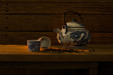 Chinese teapot and tea cup with dried tea leaf on dark brown wooden table