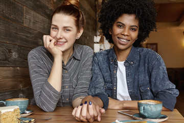 Interracial gay couple relaxing indoors. Cute Caucasian woman with hair bun holding hand of her stylish African girlfriend during lunch. Two lesbians celebrating their anniversary at restaurant