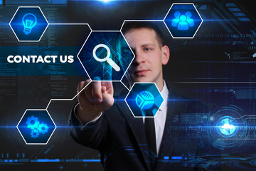 Business, Technology, Internet and network concept. Young businessman working on a virtual blackboard of the future, he sees the inscription: contact us