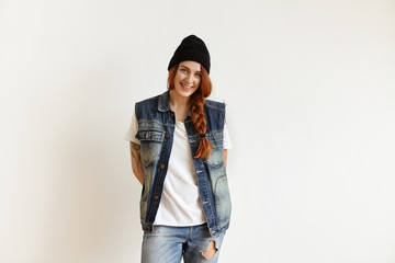 Style, fashion and beauty concept. Attractive young redhead woman having happy facial expression wearing trendy hat, denim vest and ragged jeans posing in studio, keeping hands in hip-pockets