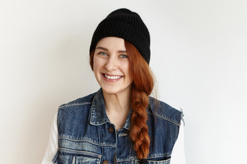 Headshot of beautiful female model with blue eyes and cute cheerful smile posing at white wall dressed in black stylish hat and denim vest, wearing her red hair in thick braid. People and lifestyle