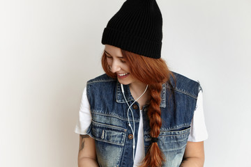 Cheerful redhead hipster girl wearing fashionable clothing having fun indoors, enjoying good music while listening to her favorite tracks in white earphones, smiling happily and looking down