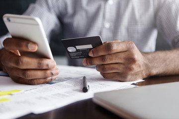 Modern technology and online shopping. African man in shirt paying for goods on internet using credit card and cell phone. Close-up of human hands, holding plastic card and mobile. Selective focus