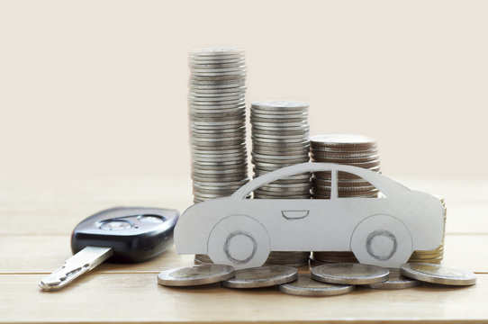 pile of money coins and key, concept in insurance,loan,finance and buying car background