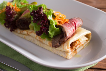 A healthy Breakfast, crepes with beef, cheese, herbs, tomatoes on a wooden table. Selective focus