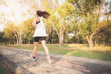 Young woman running in wood, training and exercising for trail run marathon endurance in morning sunrise. Fitness healthy lifestyle concept. Vintage effect style pictures.