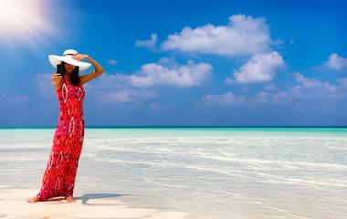 Attraktive Frau im roten Kleid macht ein Selfie Foto von sich am Strand der Malediven