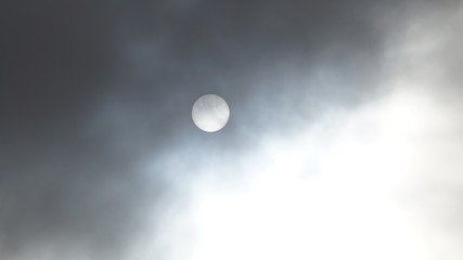 The sun hiding behind the clouds in a cloudy day