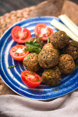Falafel with tomato and celery on a blue plate