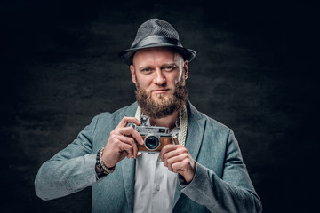 A man dressed in a grey jacket and felt hat holds an SLR photo camera.