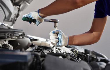 Mechanic working in auto repair garage. Car maintenance Wall mural