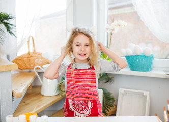 Little blonde girl showing eggs before coloring for Easter holiday at home