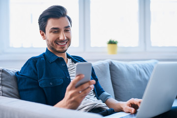 Young man sitting relaxed on sofa with laptop checking his smartphone messages
