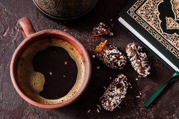 Coffee with dates fruits and Quran on dark background. Arabian style. Ramadan breakfast concept. Selective focus
