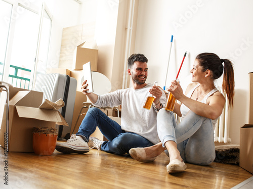 Young couple moving in new home sitting on floor and relaxing after cleaning and unpacking - Young couple modern homes ...