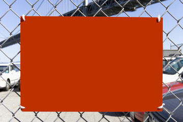 Blank red sign attached to chain link fence. Copy space.