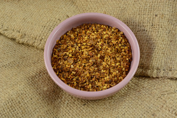 Crushed red pepper spice in pink condiment bowl on burlap