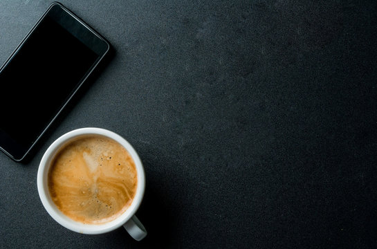Smartphone and a cup of coffee on the office black table, top view, copy space