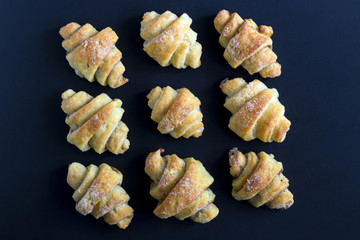 Cinnamon crescents on black background, top view