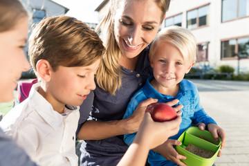 Mutter und Kinder in Schule machen Pause mit Apfel und Brotdose