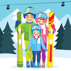 Cute happy family of three members on ski vacation wearing winter clothes