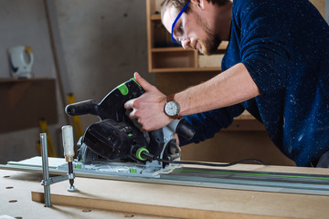 Young man working as carpenter and measuring board