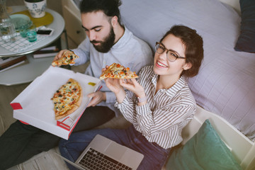 Young hipster male female couple home eating pizza with laptop