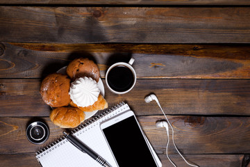 Camera lens with croissants and coffee next to notebook