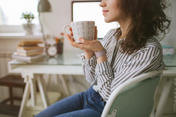 Young adult female working at home with coffee break