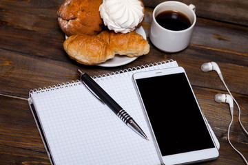 White cup of coffee with headphones and mobile phone, and lying next to notebook with pen, croissant, marshmallow