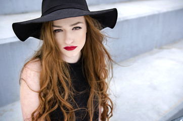 Portrait of young stylish redhead woman with hat outdoors