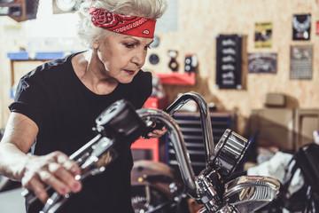 Serene female retiree situating near motorcycle