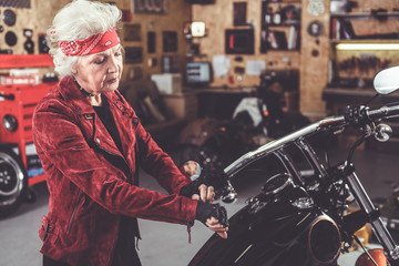 Pensioner putting on leather gloves near bike