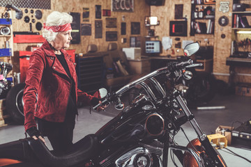 Serene grandmother situating near her motorcycle