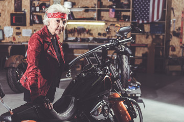 Pensive old female biker standing in mechanic shop