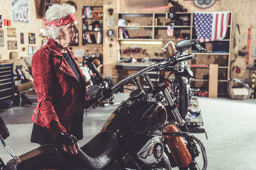 Serene granny situating next to bike in garage