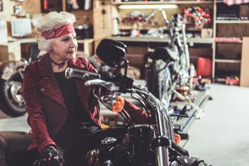Smiling pensioner sitting on motorcycle in garage