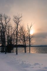 sun setting over lake in winter