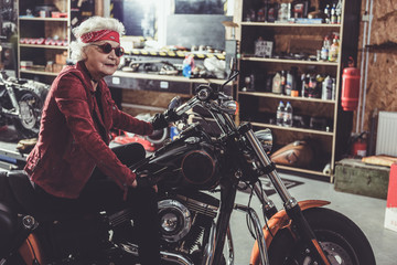 Cheerful pensioner locating on bike in garage