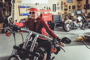 Smiling driving on motorcycle in mechanic shop