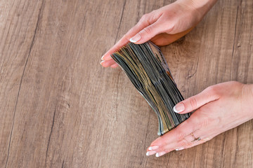 Business woman holding usa money on wooden background