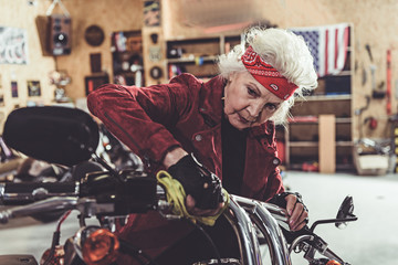 Calm female pensioner rubbing bike in garage