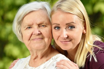 Grandmother and granddaughter. Young woman carefully takes care of an older woman.