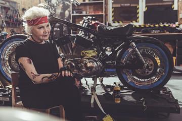 Pensive pensioner sitting next to bike