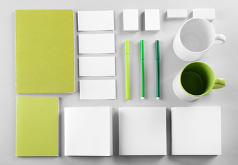 Flat lay of blank green and white goods on table