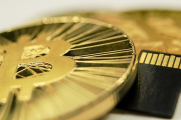 Makro detail of shiny gold Bitcoin coin and microSD memory card