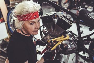 Calm pensioner reconditioning bike in garage