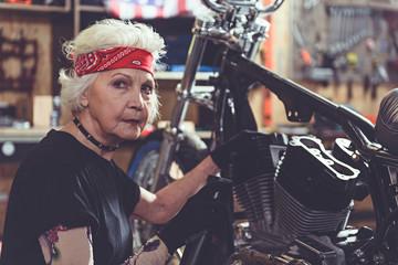 Pensive female pensioner making machine maintenance