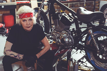 Pensive retiree sitting next to motorcycle
