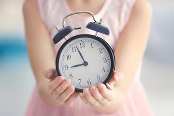 Cute little girl with alarm clock, closeup